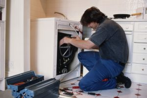 Male plumber repairing washing machine in kitchen