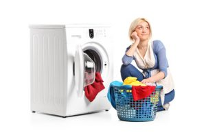 Woman in thoughts with clothes seated next to a washing machine